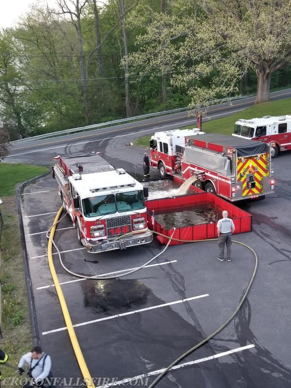 An aerial view of Tanker 88 filling a pond while Engine 148 drafts water from the pond to supply Ladder 67 (via the yellow hose line).